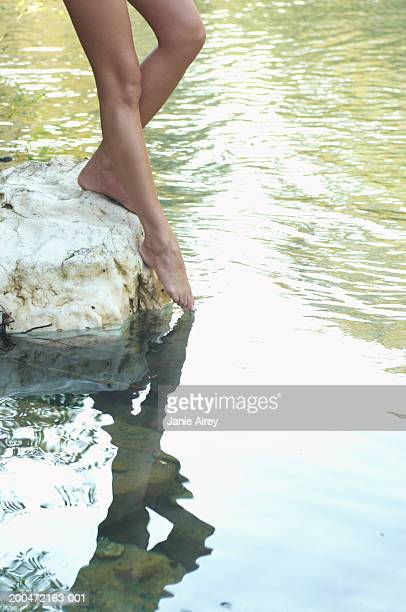 Young woman standing on rock, dipping toes in river,  low section