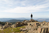 Young woman standing on rock, looking at view, Silver Star Mountain, Washington, USA