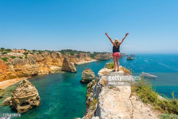 young woman standing on rocks at steep coast, stretches arms into the air, view over turquoise sea, beach praia da marinha, jagged rocky coast of sandstone, rock formations in the sea, algarve, lagos, portugal - faro stock pictures, royalty-free photos & images