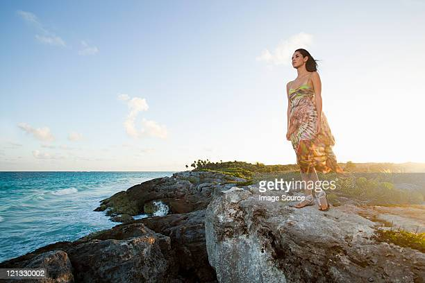 Young woman standing on rocks, Grande Cenote, Quintana
