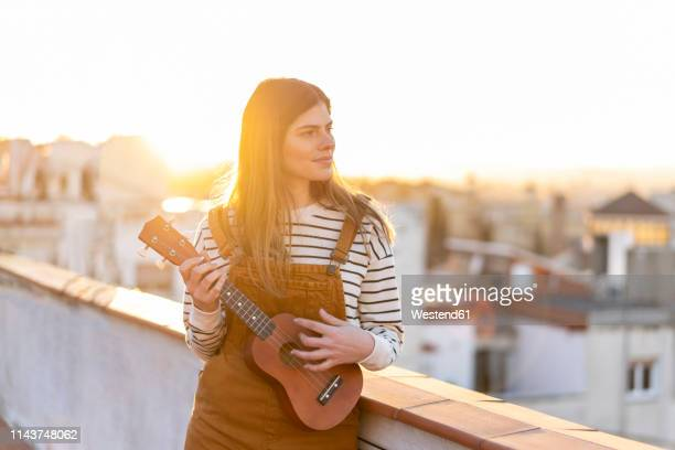 young woman standing on roof terrace in the evening playing ukulele - ukulele stock-fotos und bilder