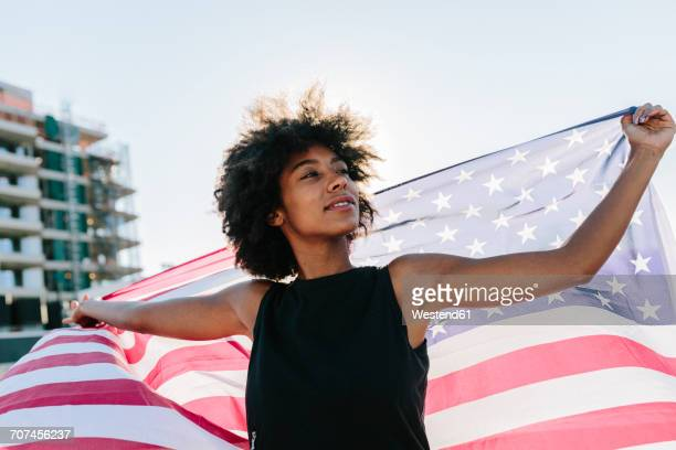 Young woman standing on rooftop holding US American flag