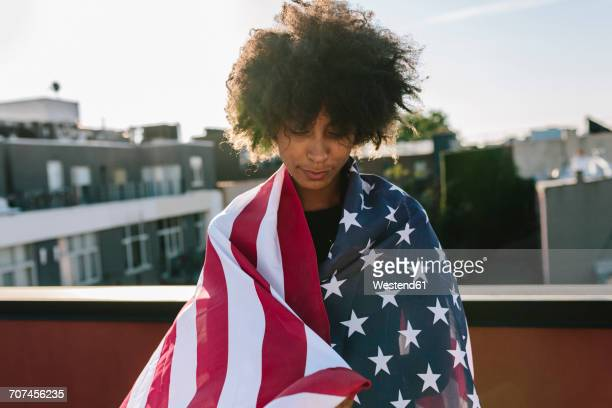 Young woman standing on rooftop warpped in US American flag