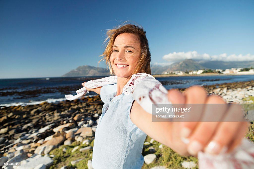 Young woman standing on sea shore with scarf blown by wind : Stock-Foto