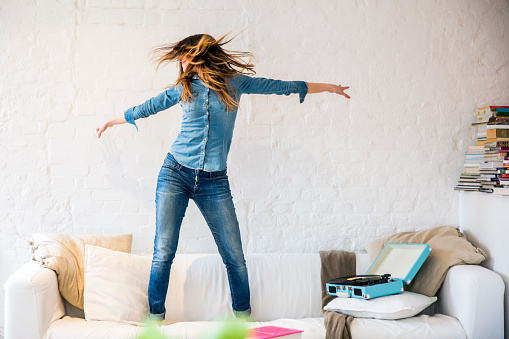 Young woman standing on sofa dancing and shaking her hair - gettyimageskorea