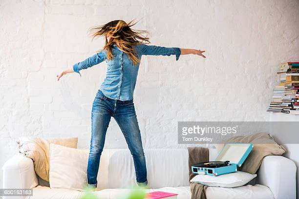 Young woman standing on sofa dancing and shaking her hair