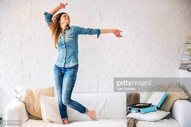young woman standing on sofa dancing to vintage record player - carefree stock pictures, royalty-free photos & images