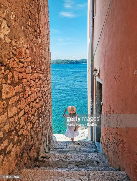 young woman standing on stairs by sea. old town, street, tourism, lifestyle. - croacia fotografías e imágenes de stock