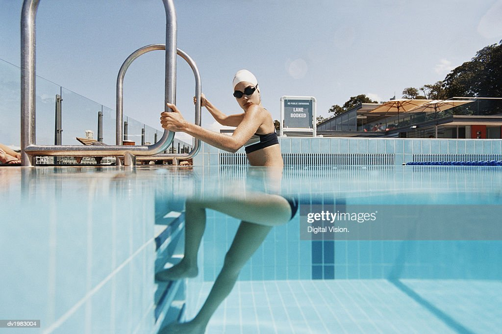Young Woman Standing on Steps at the Edge of a Swimming Pool : Stock Photo