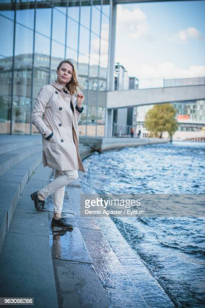 Young Woman Standing On Steps By Canal