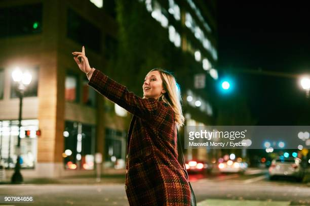 young woman standing on street at night - hail stock pictures, royalty-free photos & images