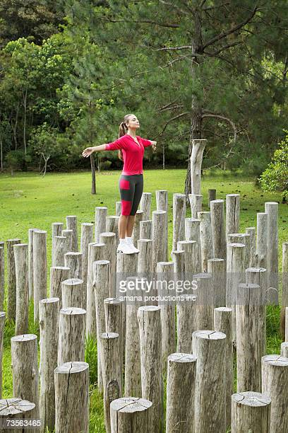 Young woman standing on stumps