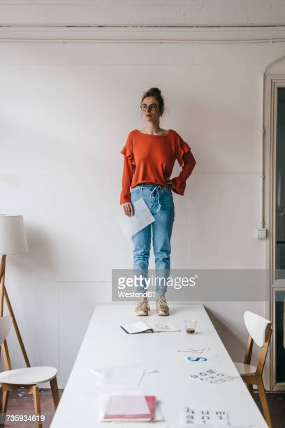 Young woman standing on table thinking
