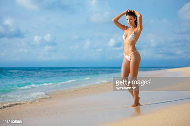 young woman standing on the beach - beautiful beach babes stock pictures, royalty-free photos & images
