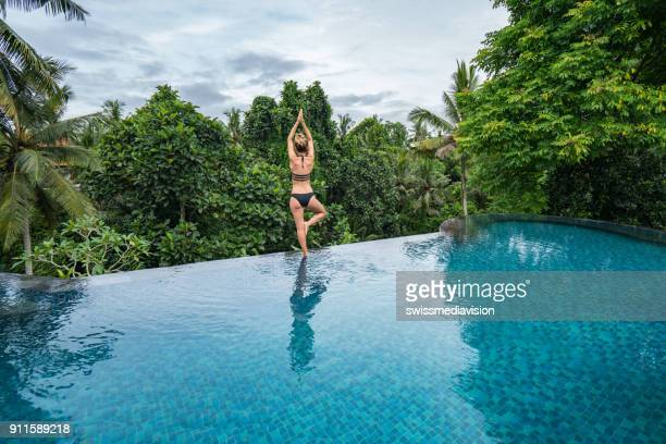 young woman standing on the edge of an infinity pool, ubud, bali - escapism stock photos and pictures