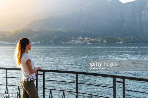young woman standing on the lakefront, admires the sunset - ammirazione foto e immagini stock