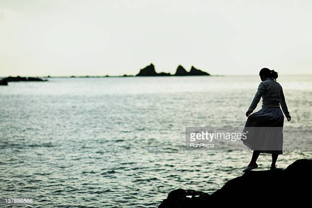 young woman standing on the rock near the sea
