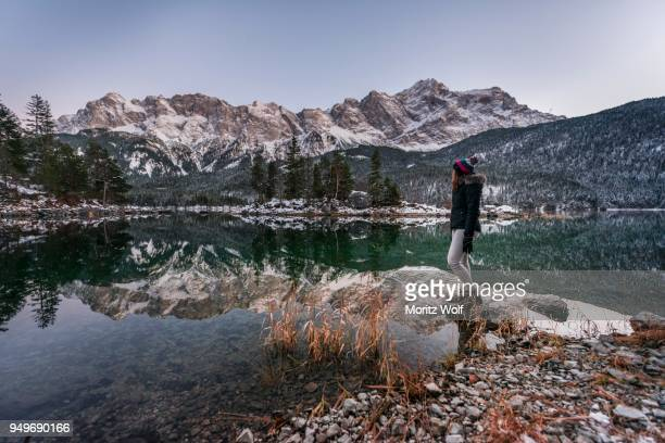 young woman standing on the shore, eibsee lake in winter with zugspitze, spiegelung, wetterstein range, upper bavaria, bavaria, germany - spiegelung stock pictures, royalty-free photos & images