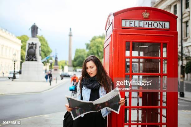 Jonge vrouw staande op de straten van Londen lezen van een tijdschrift
