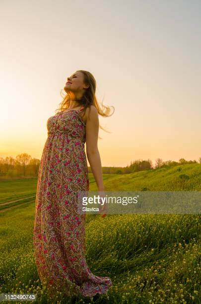 young woman standing on the summer meadow - orange dress stock pictures, royalty-free photos & images