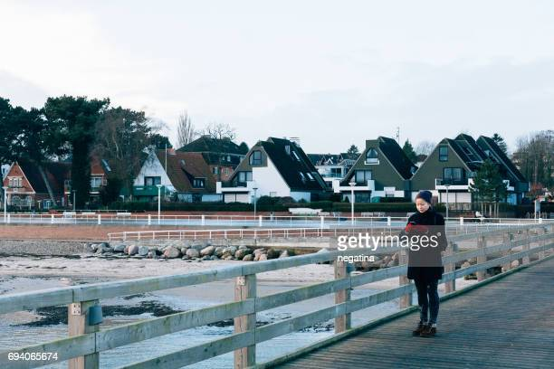 young woman standing on the Travemuende pier in front of the beach houses on winter in Germany