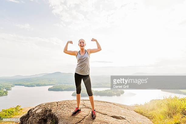 young woman standing on top of mountain and flexing muscles - flexing muscles stock pictures, royalty-free photos & images