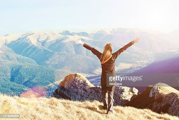 young woman standing on top of mountain