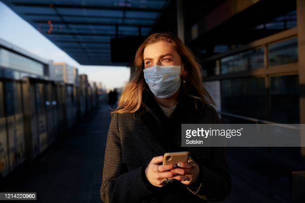 young woman standing on train station wearing protective mask, using phone - protective face mask stock pictures, royalty-free photos & images