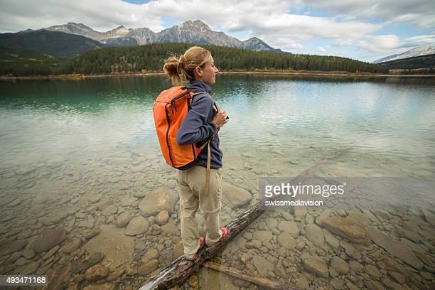 Young woman standing on tree log above lake