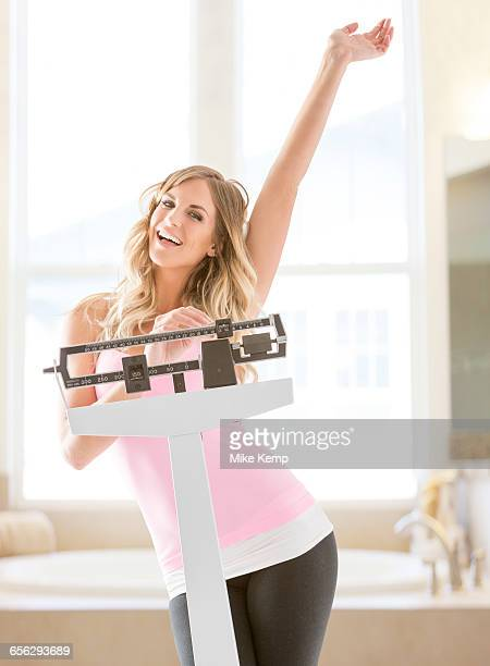 Young woman standing on weight scale in bathroom