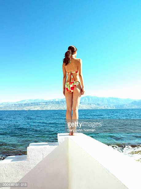 Young woman standing on white steps by sea, rear view