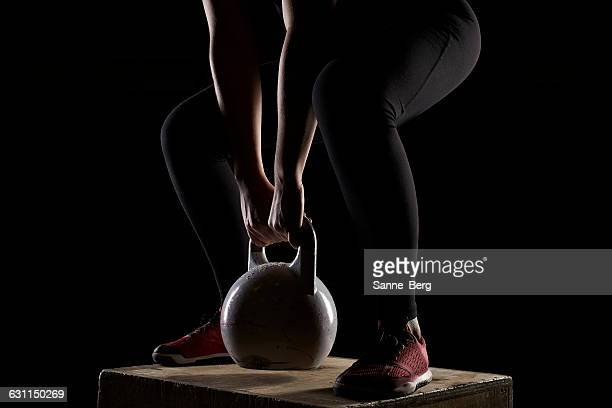 Young woman standing on wooden box lifting kettlebell weights in gym