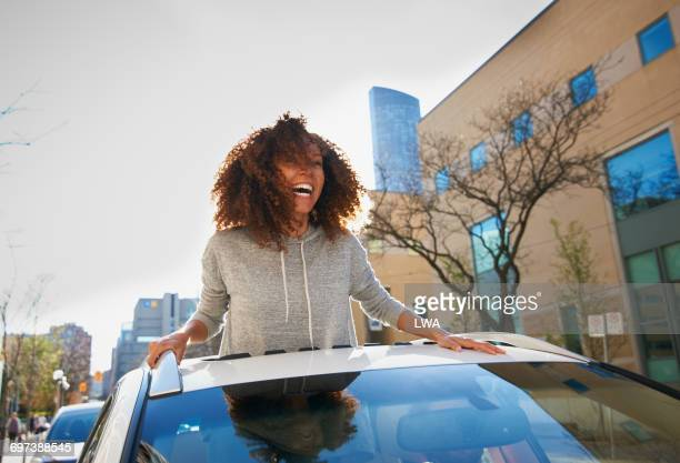 Young woman standing out of sunroof