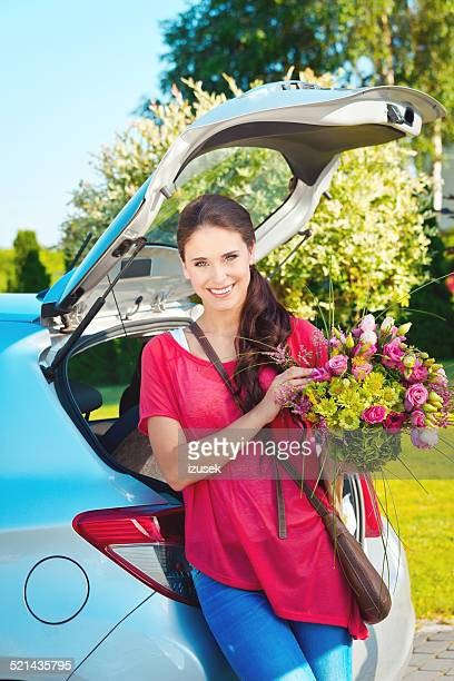 Young woman standing outdoor by car, holding flowers