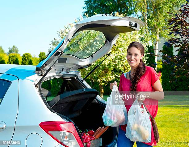 Young woman standing outdoor, holding shopping bags