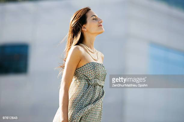 young woman standing outdoors with head back, eyes closed - strapless dress stock pictures, royalty-free photos & images