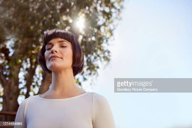 jonge vrouw die zich buiten bevindt en met gesloten ogen mediteert - mindfulness stockfoto's en -beelden
