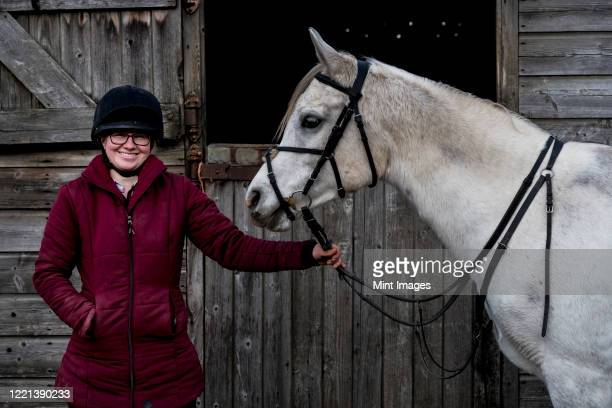 young woman standing outside stable, holding white cob horse by it's reins. - herbivorous stock pictures, royalty-free photos & images