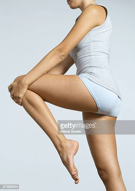 Young woman standing, stretching leg