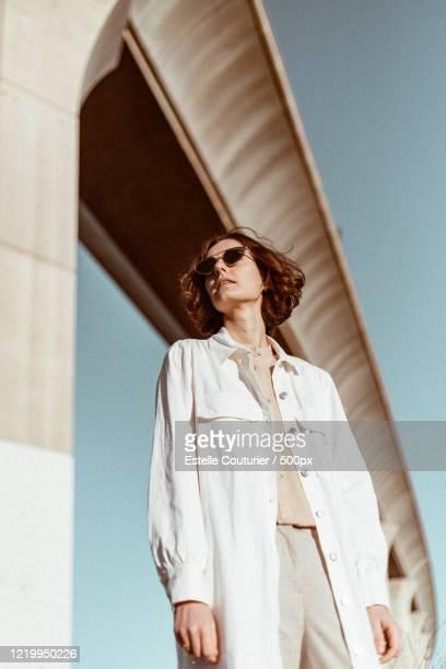 young woman standing under bridge at sunrise - óculos escuros acessório ocular - fotografias e filmes do acervo