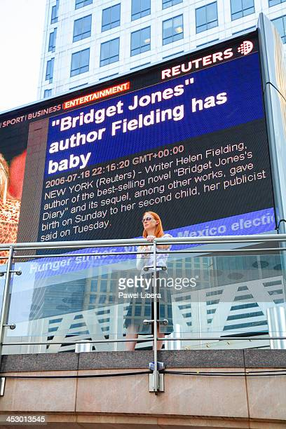 Young woman standing under Reuters digital billboard at Canary Wharf