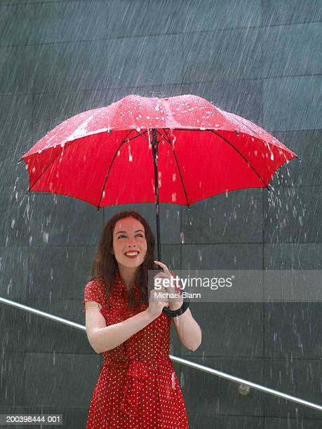 Young woman standing under umbrella in rain, looking up, close-up