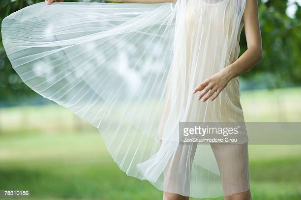 Young woman standing while dress blows in breeze, cropped view
