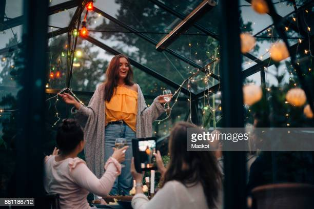 Young woman standing while singing for friends in glass cabin