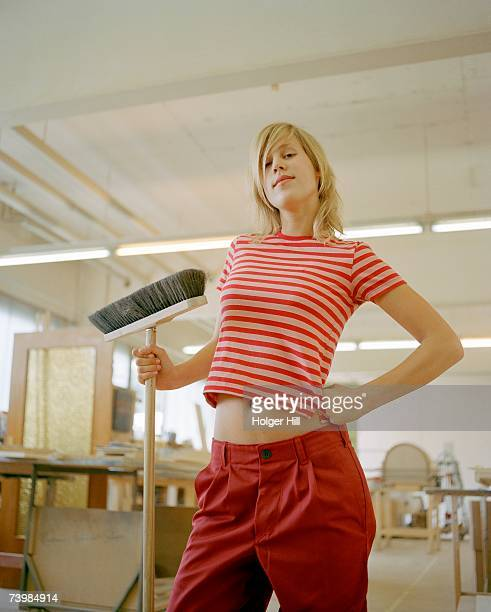 young woman standing with a hand on her hip whilst holding a broom - scope foto e immagini stock