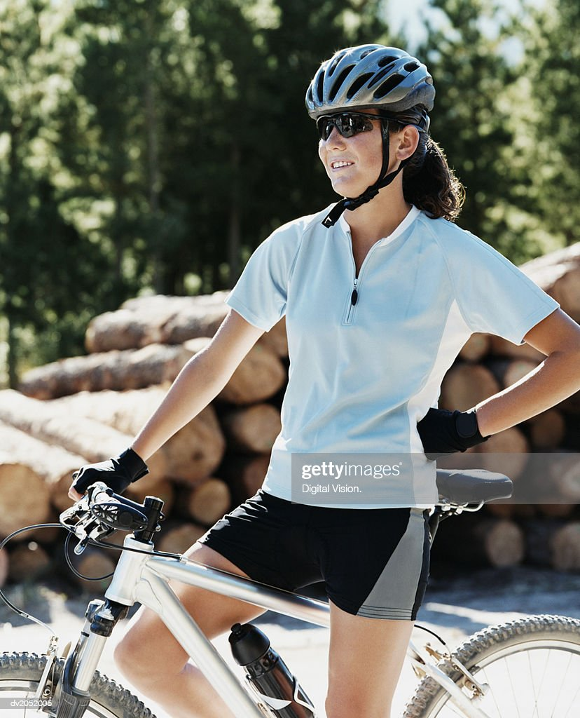 Young Woman Standing With a Mountain Bike in a Forest : Stock Photo