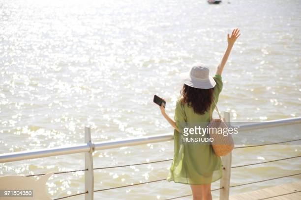 Young woman standing with arm raised by waterfront