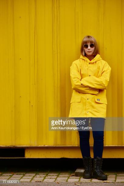 Young Woman Standing With Arms Crossed Against Yellow Cargo Container