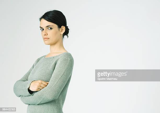 Young woman standing with arms crossed, looking at camera