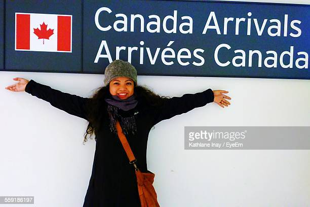 young woman standing with arms outstretched at airport - traditionally canadian stock pictures, royalty-free photos & images